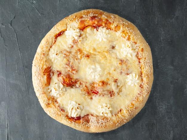 Pizza italiana. com pêra doce, mussarela, queijo holandês, queijo philadelphia, queijo sulguni, molho de tomate. lado largo. vista de cima. sobre um fundo cinza de concreto. isolado.
