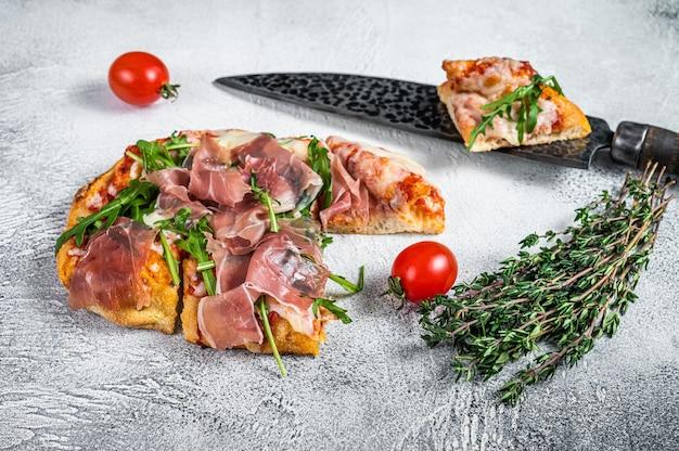 Pizza italiana com presunto de parma, rúcula e queijo na mesa da cozinha. fundo branco. vista do topo.