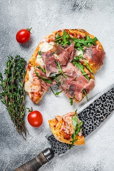 Pizza italiana com presunto de parma, rúcula e queijo na mesa da cozinha