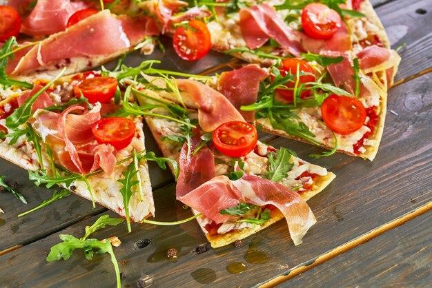 Pizza italiana com presunto, tomate, queijo e ervas na mesa de madeira vintage.