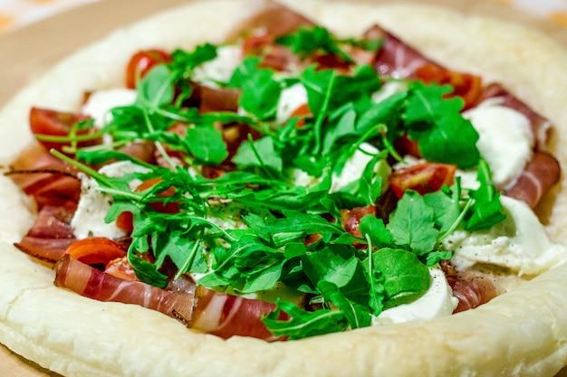 Pizza italiana com queijo mussarela, tomate, bacon e rúcula fresca na mesa de madeira.