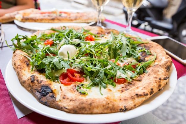 Pizza italiana com rúcula, tomate e queijo na mesa em restaurante externo