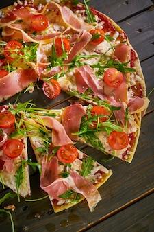 Pizza italiana com salame, tomate, queijo e ervas na mesa de madeira vintage. vista do topo