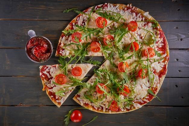 Pizza italiana com tomate, queijo e ervas na mesa de madeira vintage. vista do topo