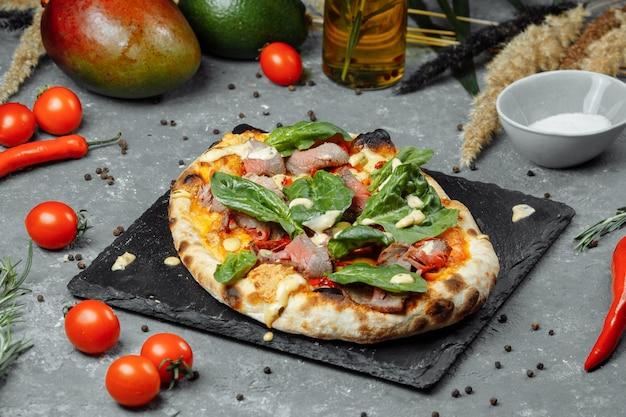 Pizza italiana de carne com rosbife, fatias de bife, queijo derretido, com rodelas de azeitona e queijo cheddar