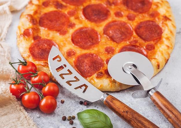 Pizza italiana de pepperoni assada fresca redonda com cortador de roda e faca com tomate e manjericão no fundo da mesa de cozinha claro.