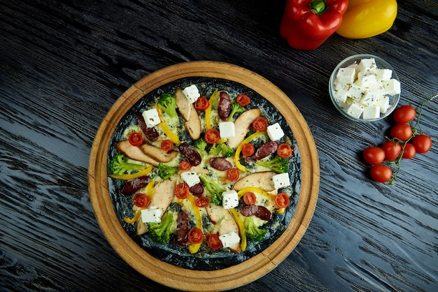 Pizza italiana deliciosa flavored quente na massa preta com carne, vegetais e queijo em uma placa de madeira escura.