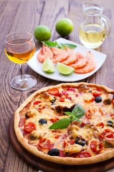 Pizza italiana e camarão na mesa de madeira