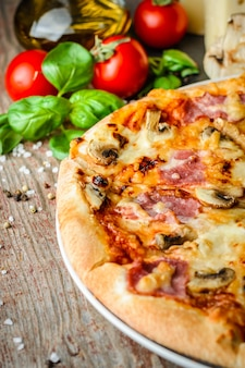 Pizza italiana e ingredientes na mesa de madeira