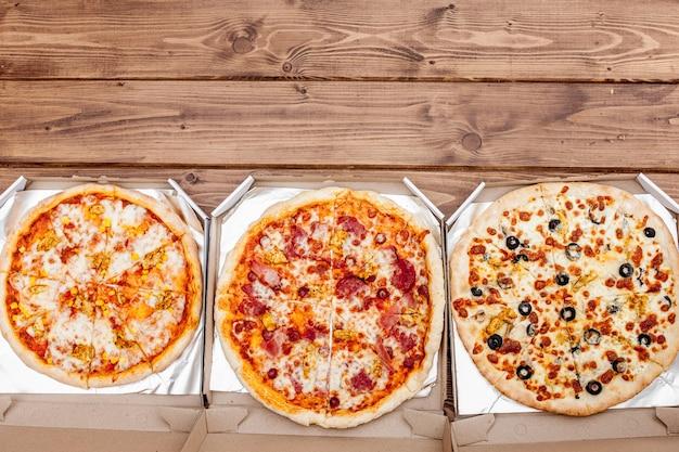 Pizza italiana em caixa de papelão na mesa de madeira. vista do topo