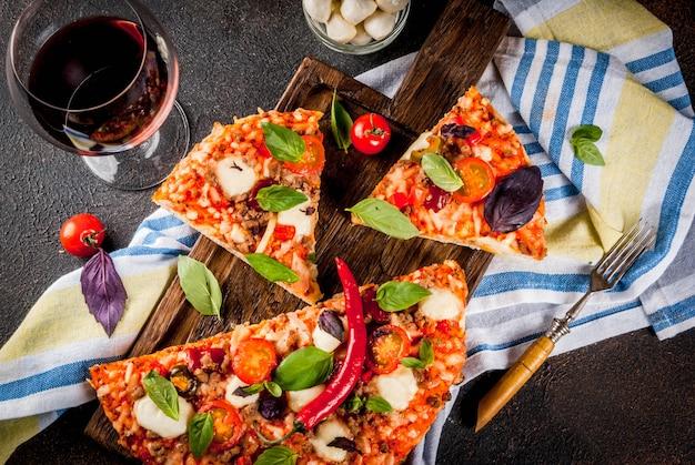 Pizza italiana fatiada e vinho tinto