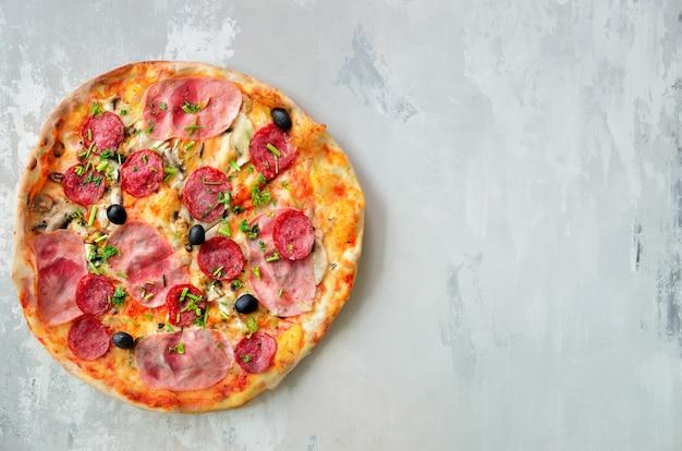 Pizza italiana fresca com cogumelos, presunto, tomate, queijo, azeitona, pimenta