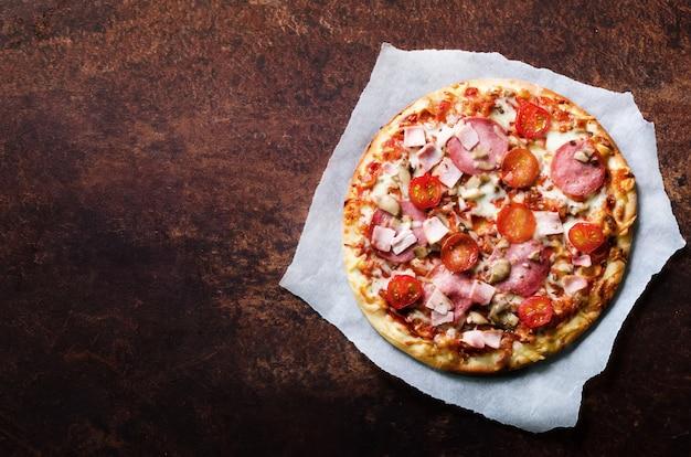 Pizza italiana fresca com cogumelos, presunto, tomate, queijo no papel de apoio,