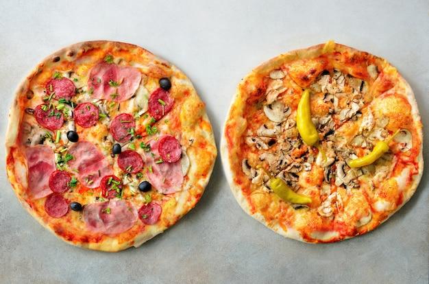 Pizza italiana fresca com cogumelos, presunto, tomates, queijo, azeitona, pimenta no fundo concreto cinzento.
