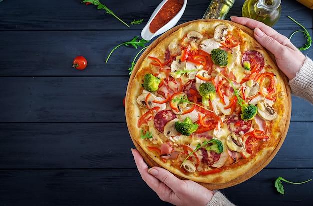 Pizza italiana fresca com filé de frango, cogumelos, presunto, salame, tomate e queijo nas mãos. comida italiana. vista do topo