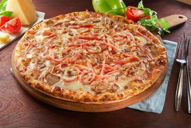 Pizza italiana inteira na mesa de madeira com ingredientes