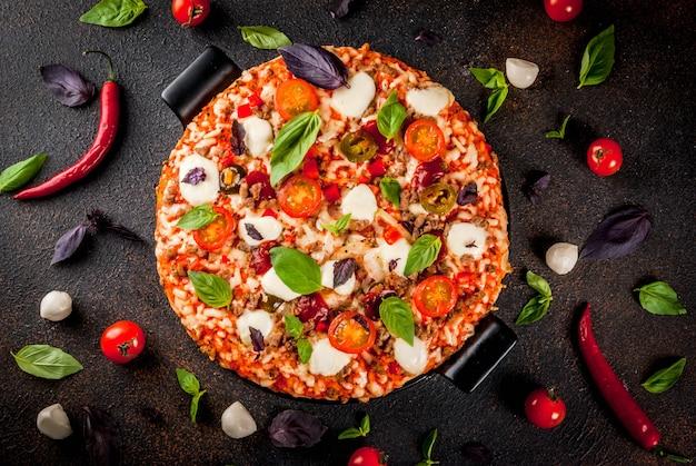 Pizza italiana na placa de grelha com vários ingredientes em fundo escuro