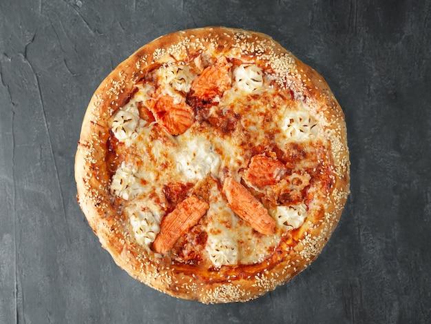 Pizza italiana. salmão do atlântico, molho de tomate, requeijão, mussarela e queijo sulguni. lado largo. vista de cima. sobre um fundo cinza de concreto. isolado.