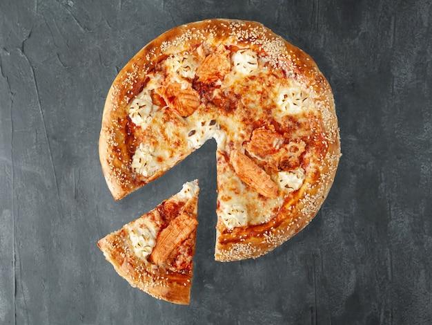 Pizza italiana. salmão do atlântico, molho de tomate, requeijão, mussarela e queijo sulguni. um pedaço é cortado da pizza. vista de cima. sobre um fundo cinza de concreto. isolado.