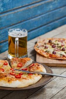 Pizza italiana, servida com copo de cerveja na prancha de madeira