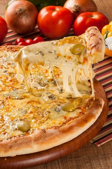 Pizza italiana tradicional com ingredientes na madeira.