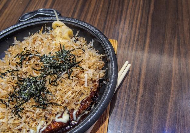 Pizza japonesa (okonomiyaki) na mesa de madeira