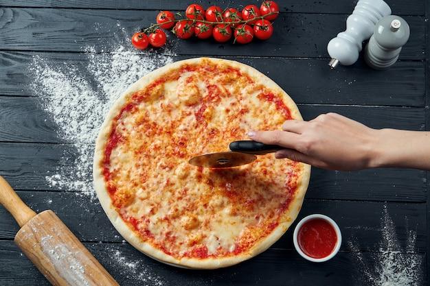 Pizza margarita assada com tomate e queijo derretido, molho vermelho e sobre uma mesa de madeira preta em uma composição com ingredientes. vista do topo. pizza cortada à mão