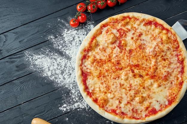 Pizza margarita assada com tomate e queijo derretido, molho vermelho e sobre uma mesa de madeira preta em uma composição com ingredientes. vista do topo