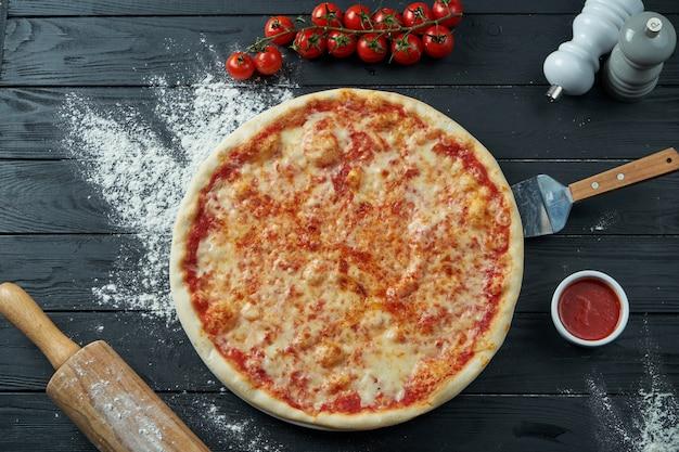 Pizza margarita assada com tomate e queijo derretido, molho vermelho sobre uma superfície de madeira preta em uma composição com ingredientes. vista do topo