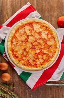 Pizza margarita fresca em mesa de madeira rústica