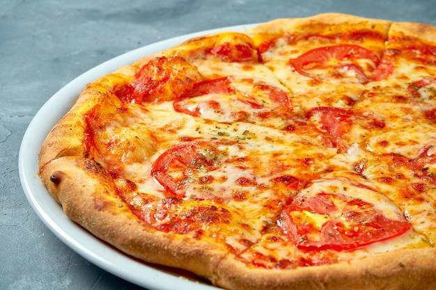 Pizza margarita italiana clássica com tomate e queijo em um prato branco no concreto