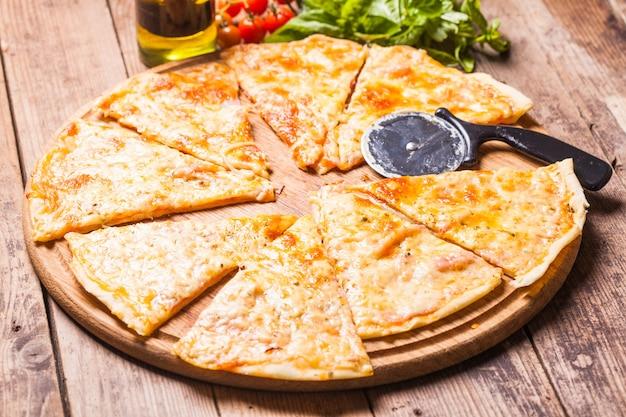 Pizza margarita na tábua de madeira e cortador de pizza