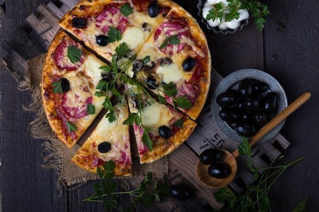 Pizza margarita ou margherita com tomate, queijo mussarela e verduras frescas. pizza margarita com faca de pizza sobre fundo na mesa de madeira rústica