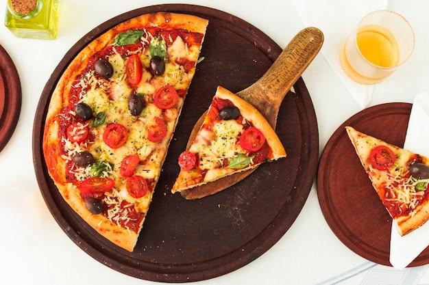 Pizza margherita caseira sobre placa circular de madeira