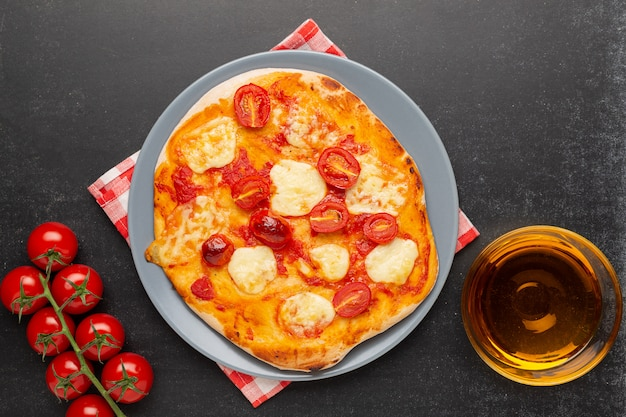 Pizza margherita com os ingredientes no fundo preto.