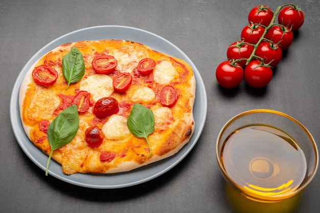 Pizza margherita com os ingredientes no fundo preto.