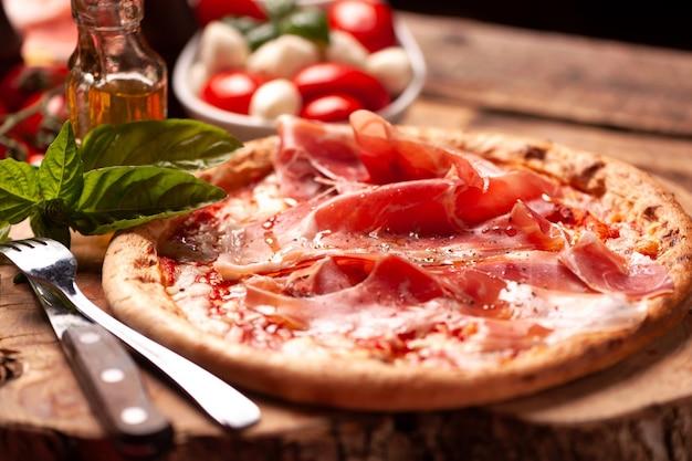 Pizza margherita com presunto de parma em mesa rústica