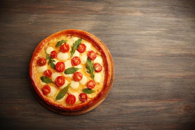 Pizza margherita com rúcula em madeira