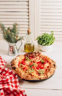 Pizza margherita com rúcula fresca e enfeites de natal em madeira branca