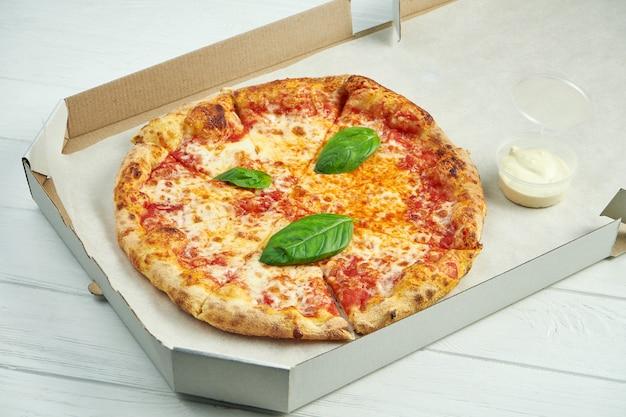 Pizza margherita com tomate, manjericão e mussarela em uma caixa de papelão com molho para os lados em uma mesa de madeira