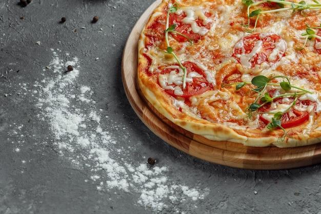 Pizza margherita na mesa de pedra preta, vista superior. pizza margarita com tomate, manjericão e queijo mussarela close-up