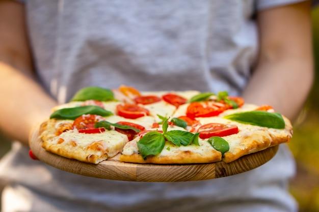 Pizza margherita nas mãos