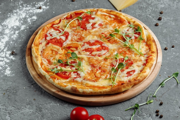 Pizza margherita no fundo de pedra preto, vista superior. pizza margarita com tomate, manjericão e queijo mussarela close-up