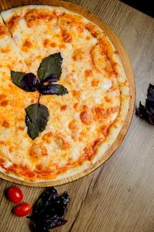 Pizza margherita servida com folhas de manjericão