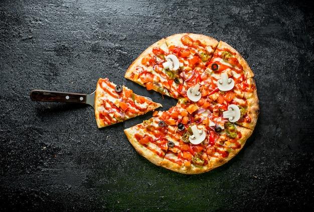 Pizza mexicana fatiada em mesa preta rústica