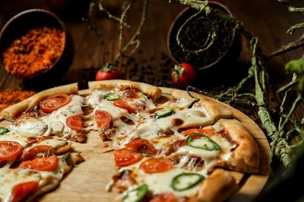 Pizza mista com muito queijo e tomate