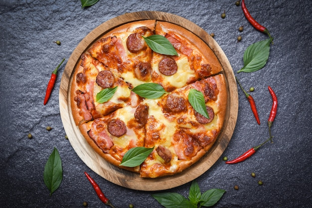 Pizza na bandeja de madeira e pimentão manjericão folha vista superior
