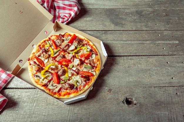 Pizza na caixa de entrega na mesa de madeira por toalha de mesa