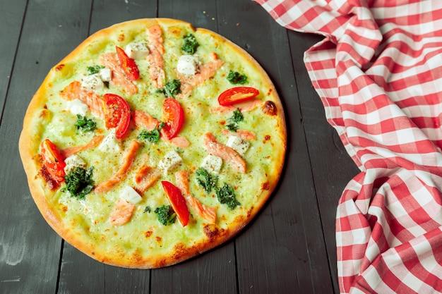 Pizza na mesa de madeira ao lado do pano de mesa