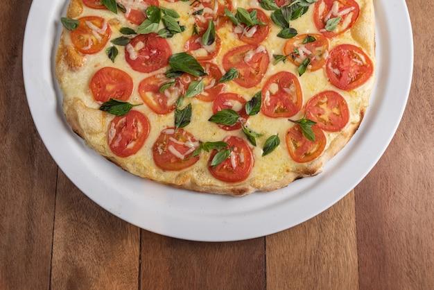 Pizza na mesa de madeira marrom